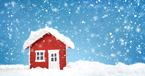 Small red house model covered with snow